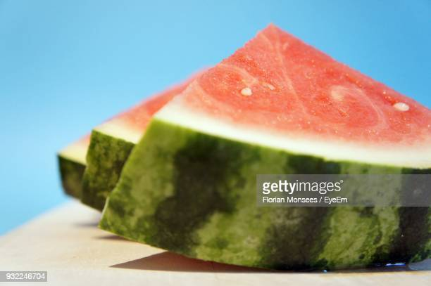 Close-Up Of Watermelon Slices On Table Against Blue Background