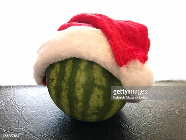 close-up of watermelon with santa hat on table against white background - santa hat stock photos and pictures