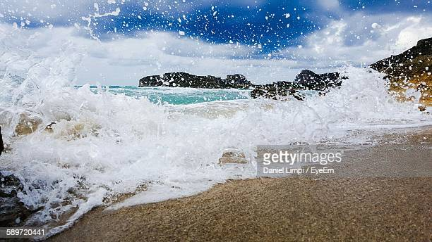 Close-Up Of Wave Splashing At Shore Against Sky