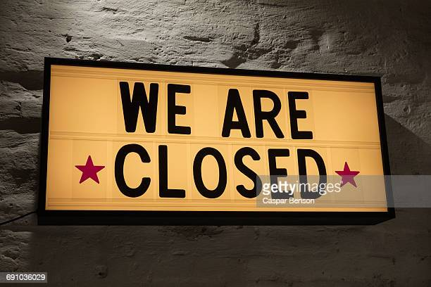 Close-up of We Are Closed signboard against gray wall