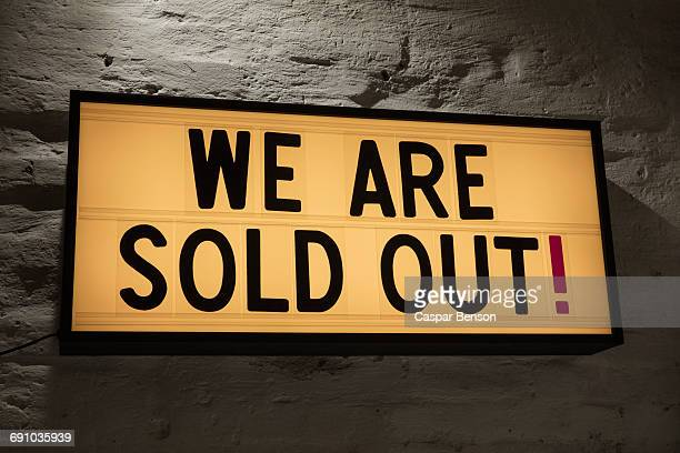 Close-up of We Are Sold Out signboard against gray wall