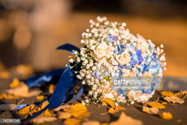 Close-Up Of Wedding Bouquet With Autumn Leaves On Footpath