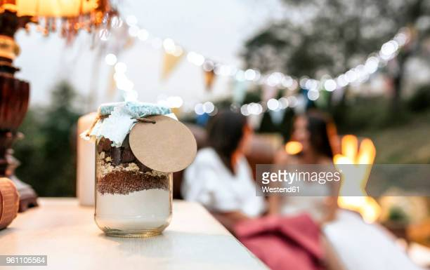 close-up of wedding gift jar with ingredients to make homemade chocolate cookies - persona in secondo piano foto e immagini stock