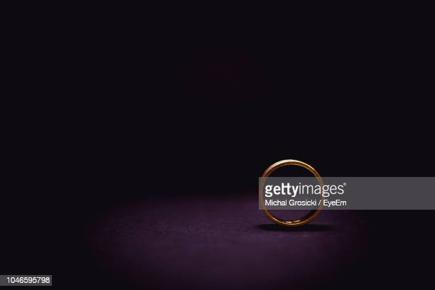 close-up of wedding ring on table against black background - wedding ring stock pictures, royalty-free photos & images