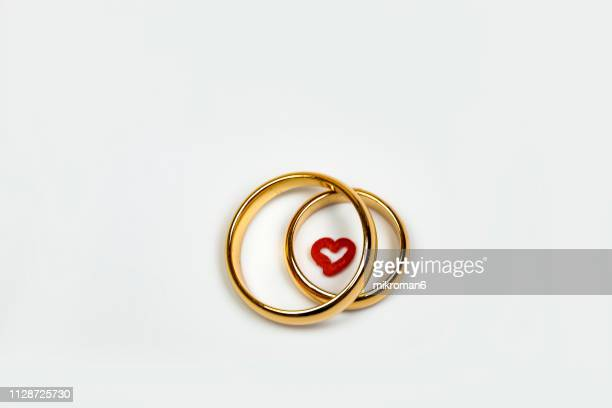 close-up of wedding rings and heart - his and hers stock pictures, royalty-free photos & images