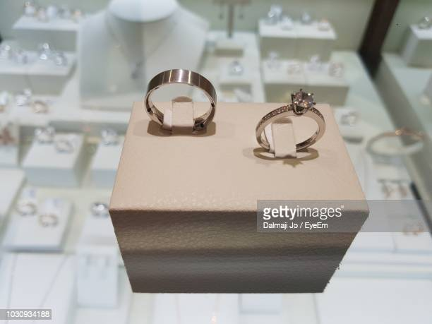 close-up of wedding rings on display cabinet in shop - jewelry store stock pictures, royalty-free photos & images