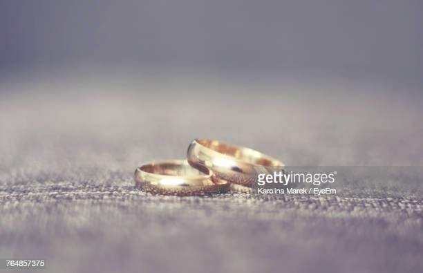 close-up of wedding rings on floor - wedding ring stock pictures, royalty-free photos & images