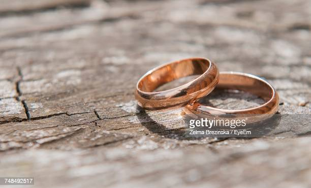 close-up of wedding rings on old wooden table during sunny day - wedding ring stock pictures, royalty-free photos & images