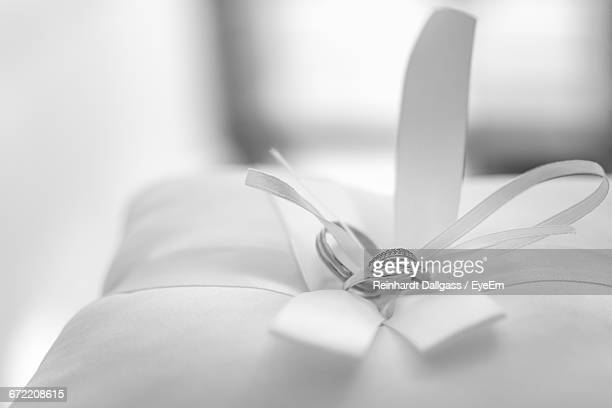 Close-Up Of Wedding Rings On Pillow At Home