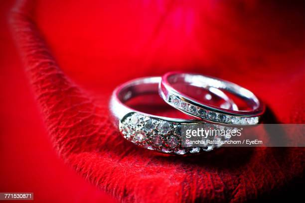Close-Up Of Wedding Rings On Red Petal