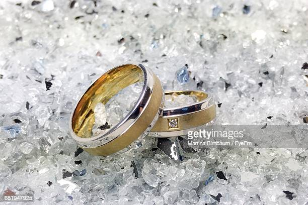 Close Up Of Wedding Rings On Shattered Gl