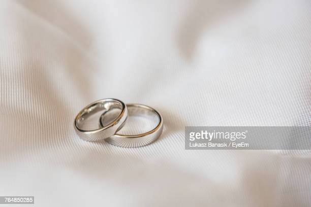 close-up of wedding rings on tablecloth - wedding ring stock pictures, royalty-free photos & images