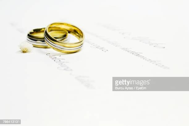 Close-Up Of Wedding Rings On White Paper