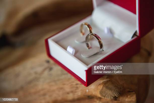 close-up of wedding rings on wooden table - engagement ring box stock photos and pictures