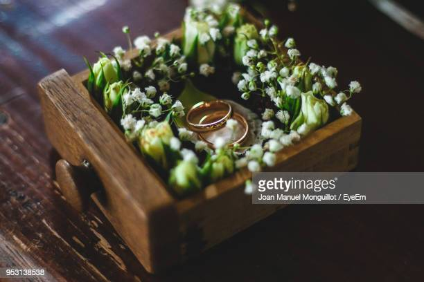 close-up of wedding rings with flowers in box on table - engagement ring box stock photos and pictures
