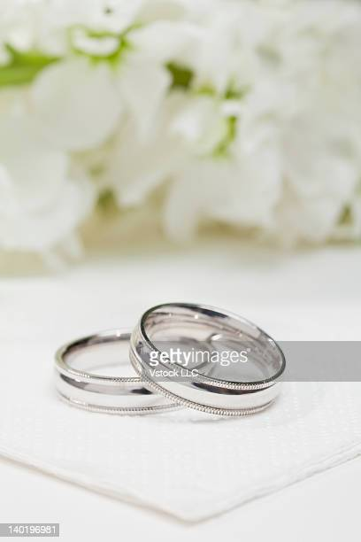 Close-up of wedding rings with white flowers in background