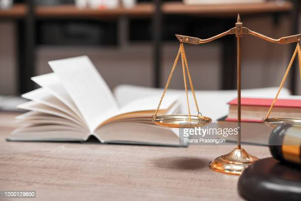 close-up of weight scale and gavel on table - defendant stock pictures, royalty-free photos & images