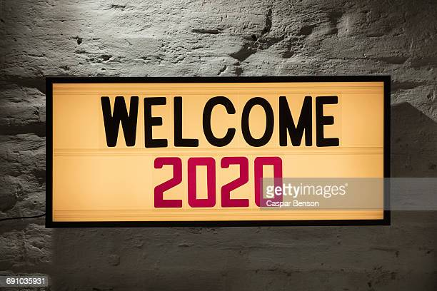 Close-up of Welcome 2020 signboard against gray wall