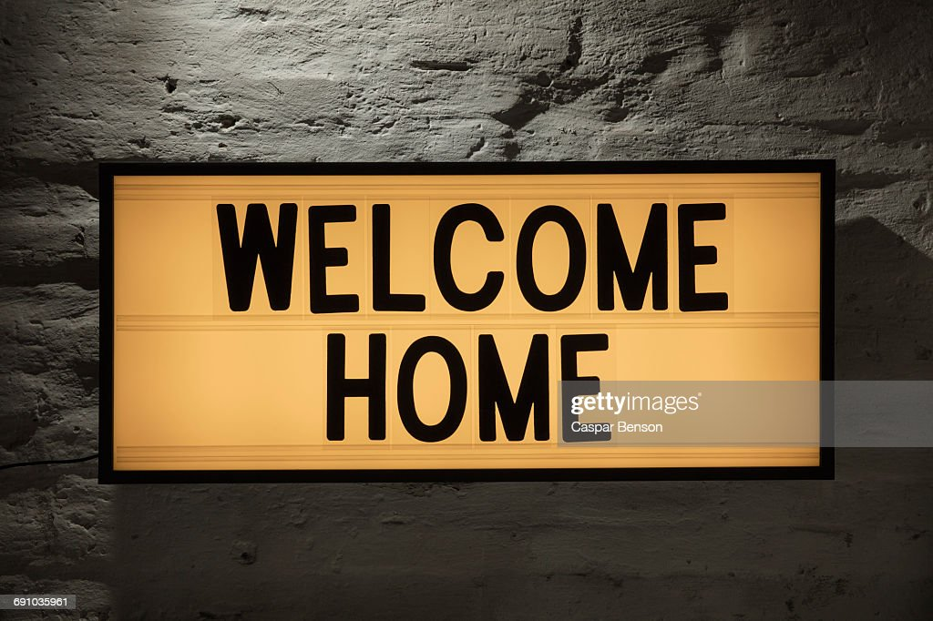 Close-up of Welcome Home signboard against gray wall : Stock Photo