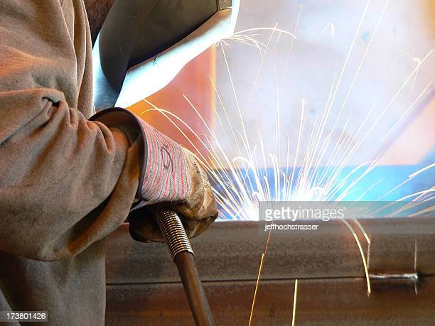 Closeup of welder with dramatic flairs from his tools