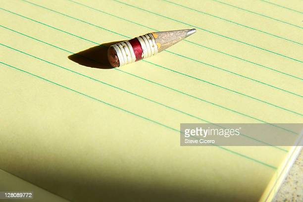 Close-up of well used pencil on yellow notepad