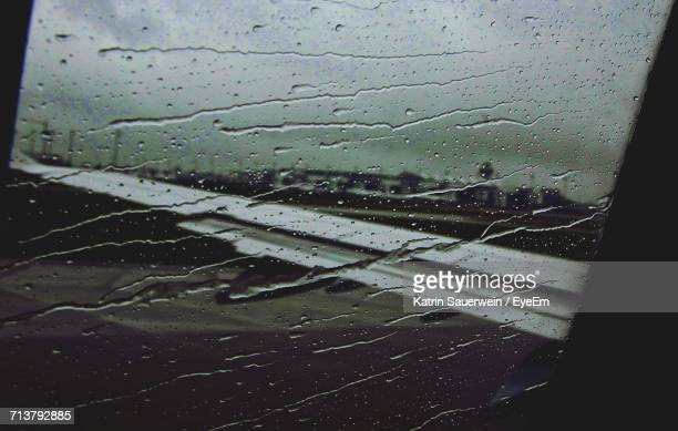 Close-Up Of Wet Airplane Window In Rainy Season