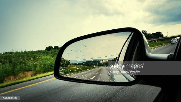 close-up of wet car side-view mirror on country road against cloudy sky - side view mirror stock photos and pictures