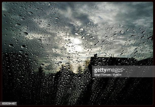 Close-Up Of Wet Car Window Against Cloudy Sky During Rainy Season