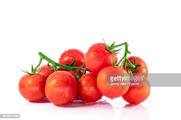 Close-Up Of Wet Cherry Tomatoes Against White Background