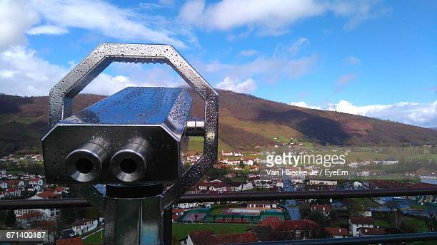 close-up of wet coin-operated binoculars by residential district against sky during monsoon - saint jean pied de port stock photos and pictures
