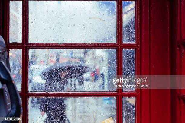 close-up of wet glass window in city during rainy season - mcgregor stock pictures, royalty-free photos & images