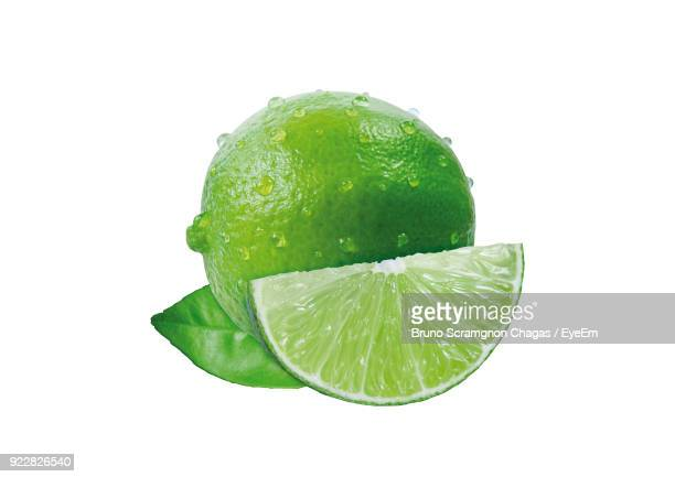 close-up of wet lime against white background - limette stock-fotos und bilder