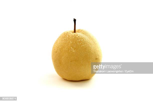 close-up of wet pear against white background - pear stock pictures, royalty-free photos & images