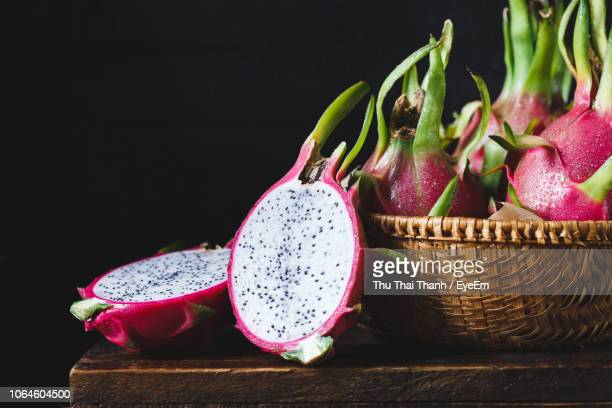 close-up of wet pitayas on wooden table against black background - dragon fruit stock pictures, royalty-free photos & images