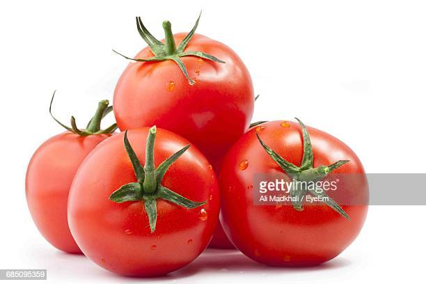 Close-Up Of Wet Red Tomatoes Against White Background