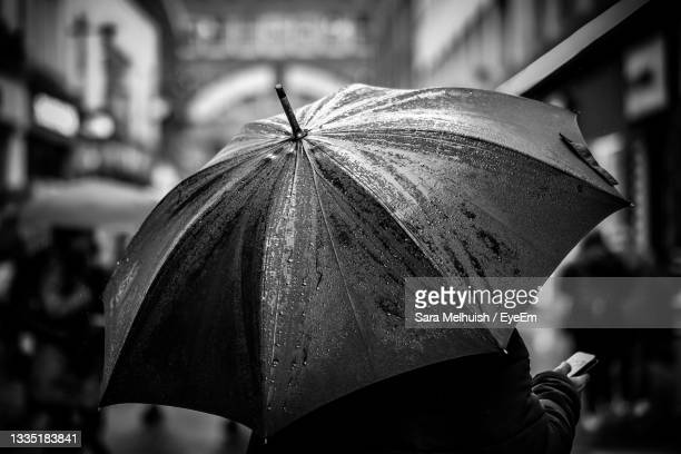 close-up of wet umbrella on street - rain stock pictures, royalty-free photos & images