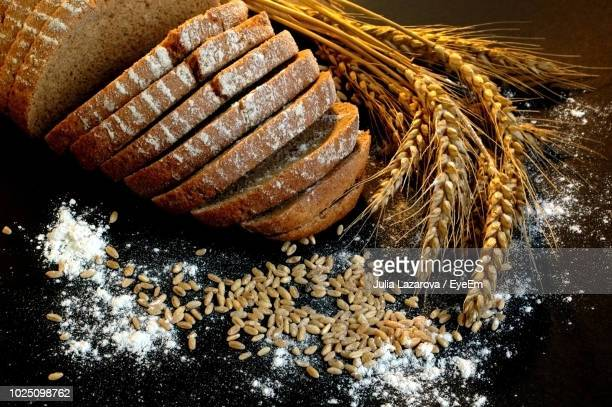 close-up of wheat and brown breads over black background - rye grain stock pictures, royalty-free photos & images