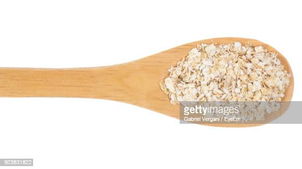 Close-Up Of Wheat On Wooden Spoon Over White Background