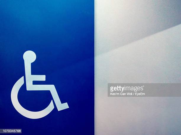 close-up of wheelchair access sign on wall - disabled sign stock photos and pictures
