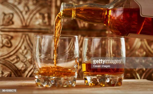 close-up of whiskey being poured into glass on table - scotch whiskey stock pictures, royalty-free photos & images