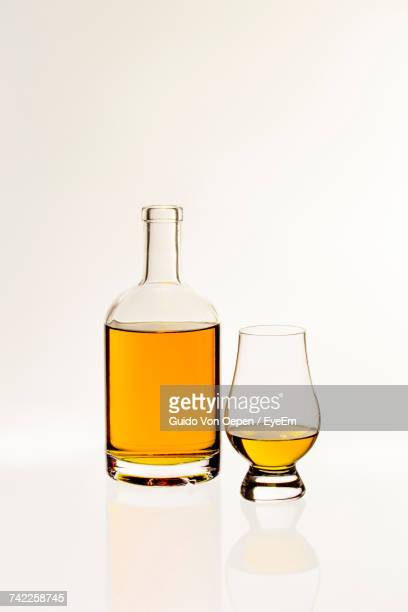 close-up of whiskey bottle against white background - whisky stock photos and pictures