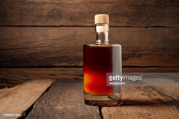 close-up of whiskey bottle on wooden table against wooden wall. - whisky stock pictures, royalty-free photos & images