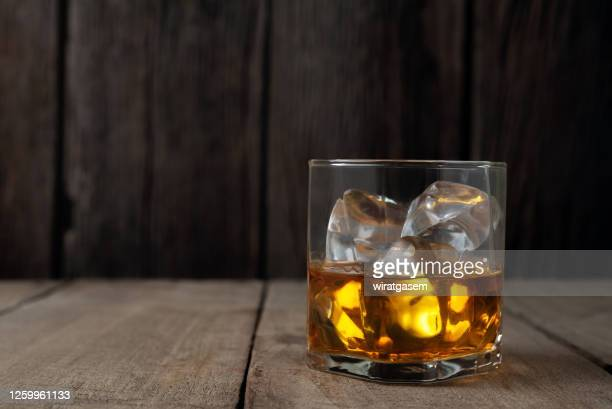 close-up of whiskey bottle on wooden table against wooden wall. - bourbon whiskey stock pictures, royalty-free photos & images