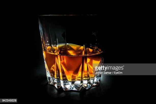 close-up of whiskey glass against black background - kristallglas stock-fotos und bilder