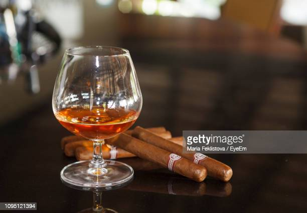 close-up of whiskey in glass by cigars on table in restaurant - cigar stock pictures, royalty-free photos & images