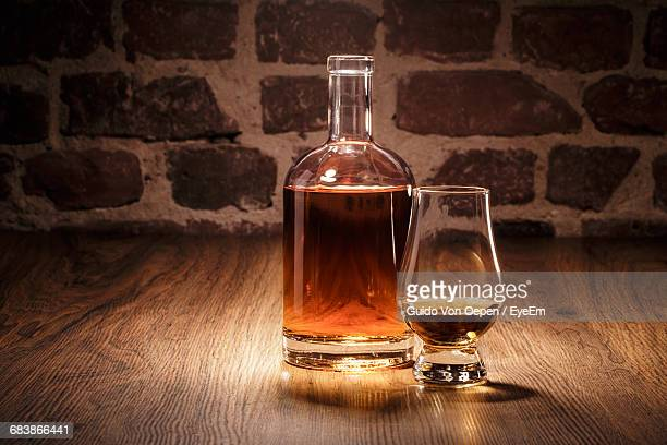 Close-Up Of Whisky Bottle And Glass On Hardwood Floor Against Stone Wall