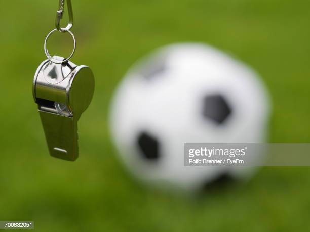 Close-Up Of Whistle With Soccer Ball On Field