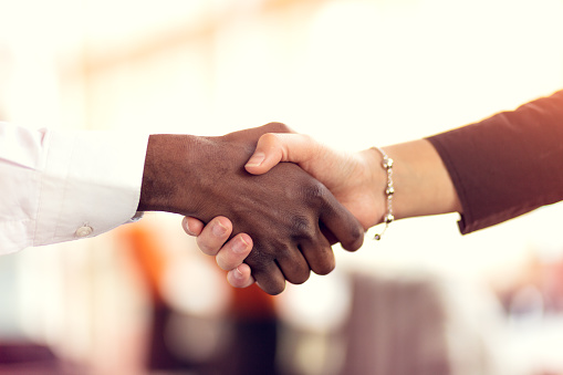Closeup of White and Black shaking hands over a deal 918730008