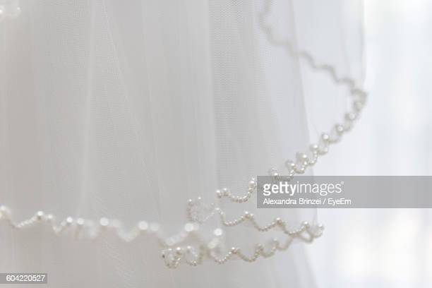 close-up of white beads on lace - frilly stock photos and pictures