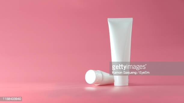 close-up of white cosmetic plastic tubes on pink background - cosmetics stock pictures, royalty-free photos & images